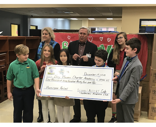 Kennedy and Avery present the money they raised to Bay Haven Academy.